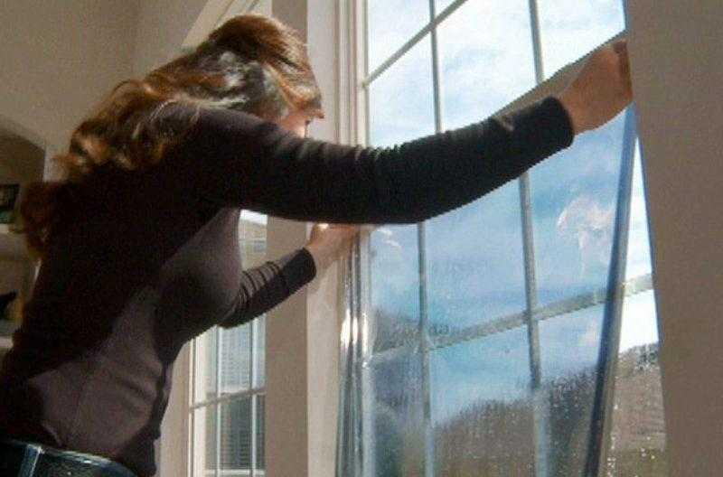 Женщина приклеивает пленочное покрытие на стекло