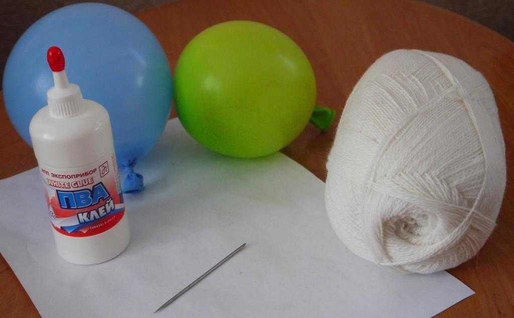 Воздушные шарики, клей ПВА, игла и моток пряжи фото