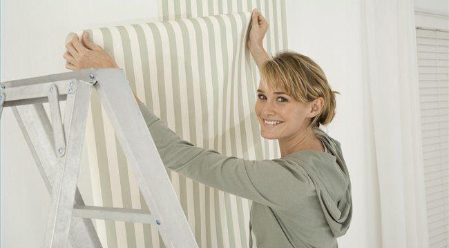 Девушка клеит листы на стены фото